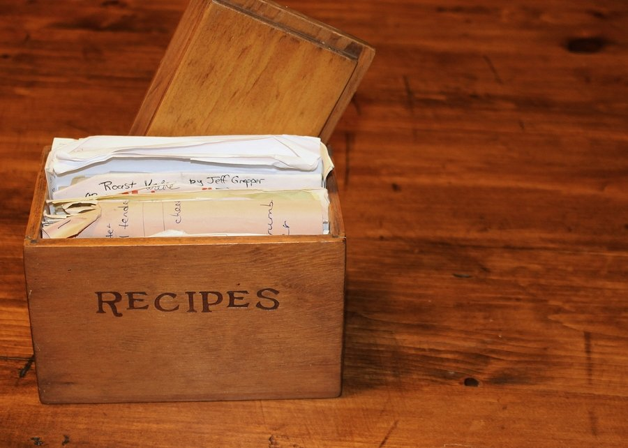 An old, wooden recipe box sitting on a table.